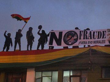 Policías bolivianos despliegan una pancarta en el techo de una unidad policial en Cochabamba