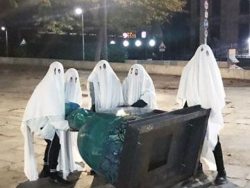 Un grupo de personas con sábanas vuelcan una de las meninas colocadas en Madrid