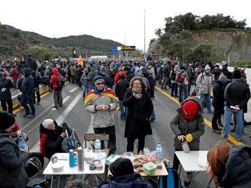 Manifestantes se avituallan durante el bloqueo de la autopista que enlaza España y Francia