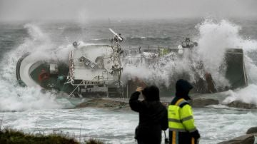 Las olas zarandean un barco en Porto do Son, A Coruña