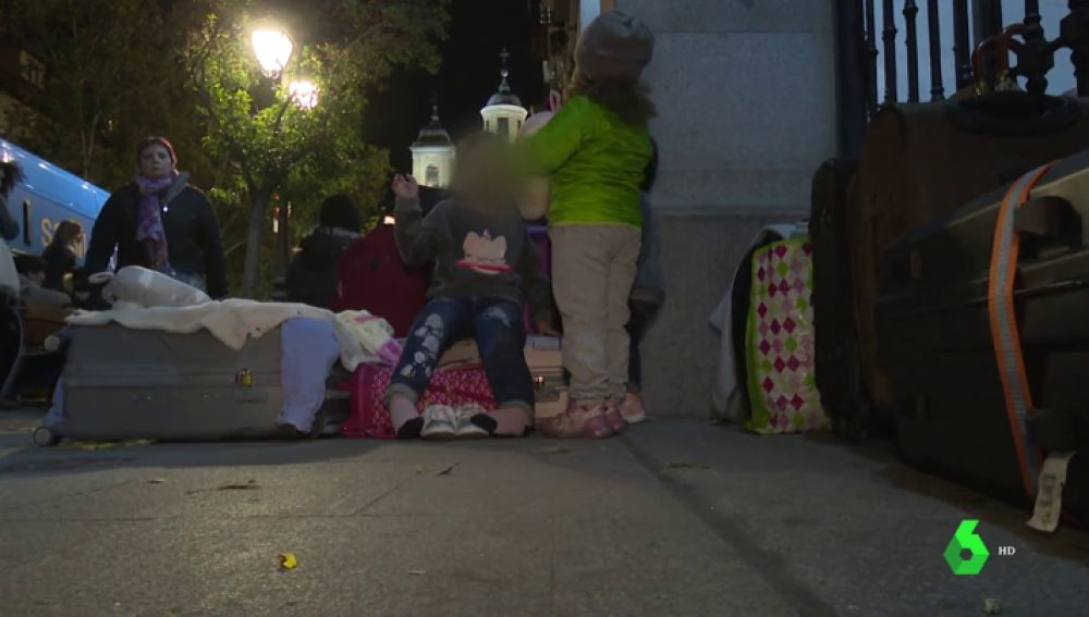 Familias esperando para entrar en un albergue