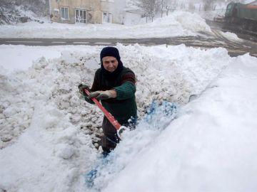 Un hombre retira la nieve sobre su vehículo en el alto del pueblo lucense de O Poio