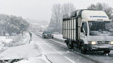 Varios vehículos circulan bajo la nieve en el municipio leonés de Riello