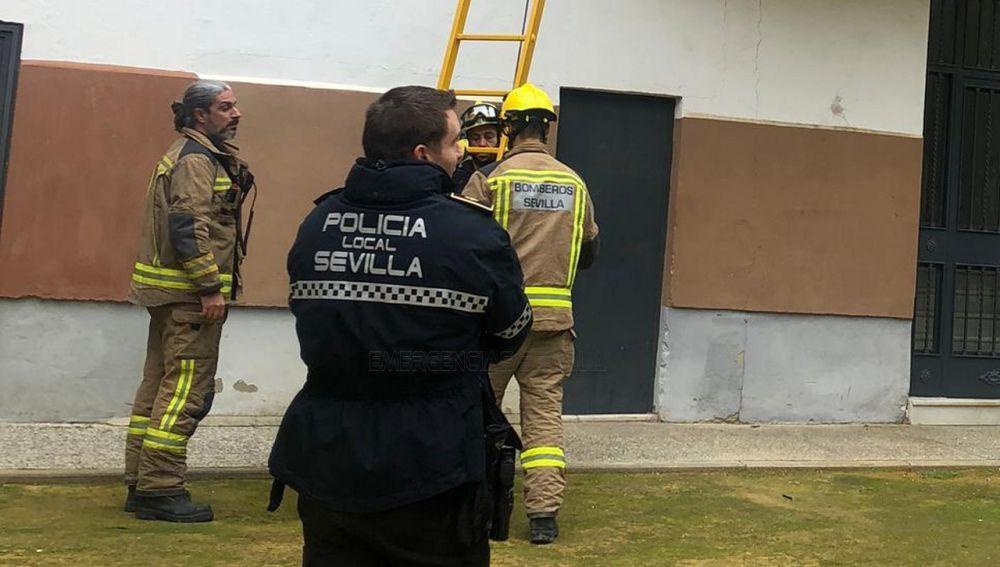 Un policía local y dos bomberos trabajando en el rescate de la menor