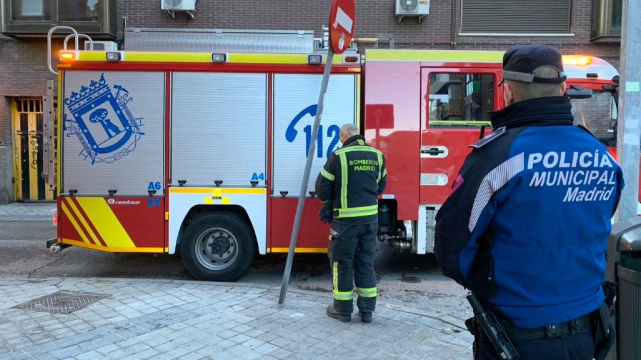Un bombero y un policía tras el incendio declarado en Vallecas