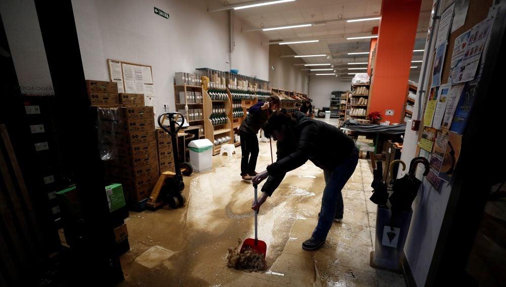 Varios empleados retiran agua y barro del interior de su comercio