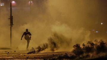 Un manifestante da una patada a una granada de gas lacrimógeno