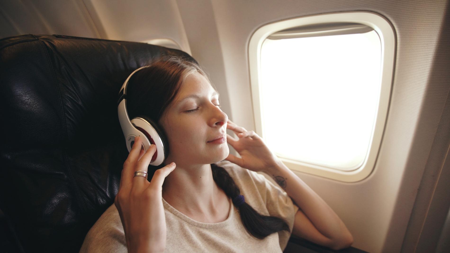 Joven escucha música con auriculares inalámbricos en el avión