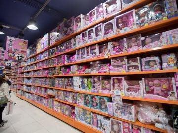 Una mujer mira una estantería llena de juguetes en una gran superficie