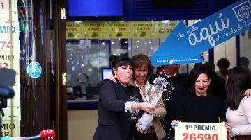 Un grupo de personas celebran en la administración madrileña de Doña Manolita que ha vendido el número 26.590
