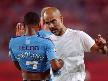 Guardiola habla con Sterling durante un partido