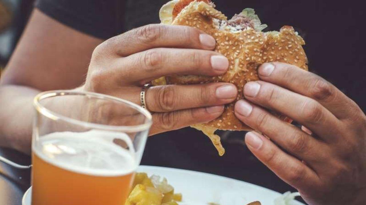 Imagen de archivo de un hombre comiendo una hamburguesa
