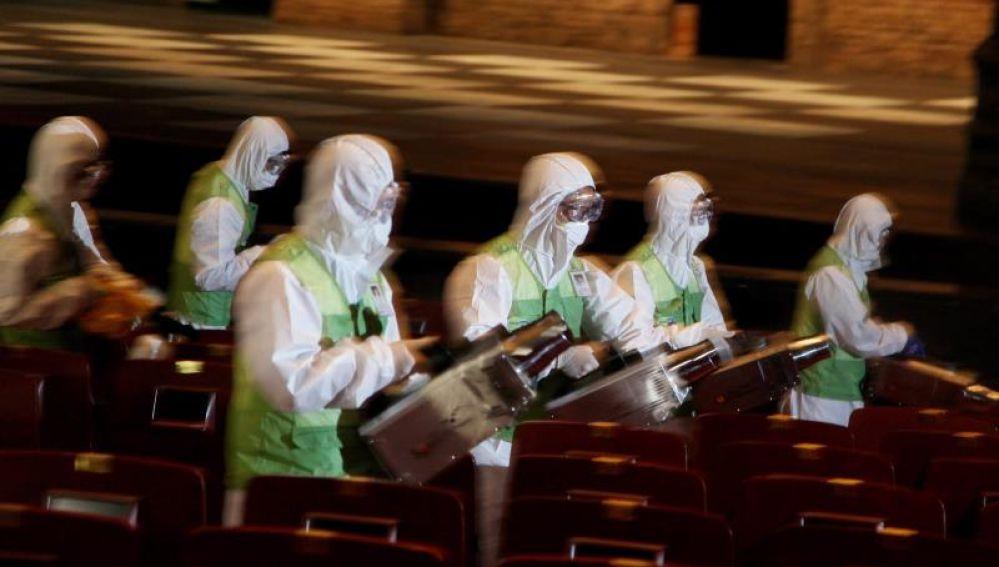 Miembros de una brigada de salud fumigan un teatro en Seúl