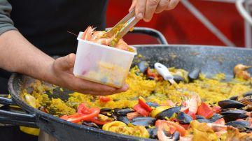 Imagen de una persona cocinando una paella.