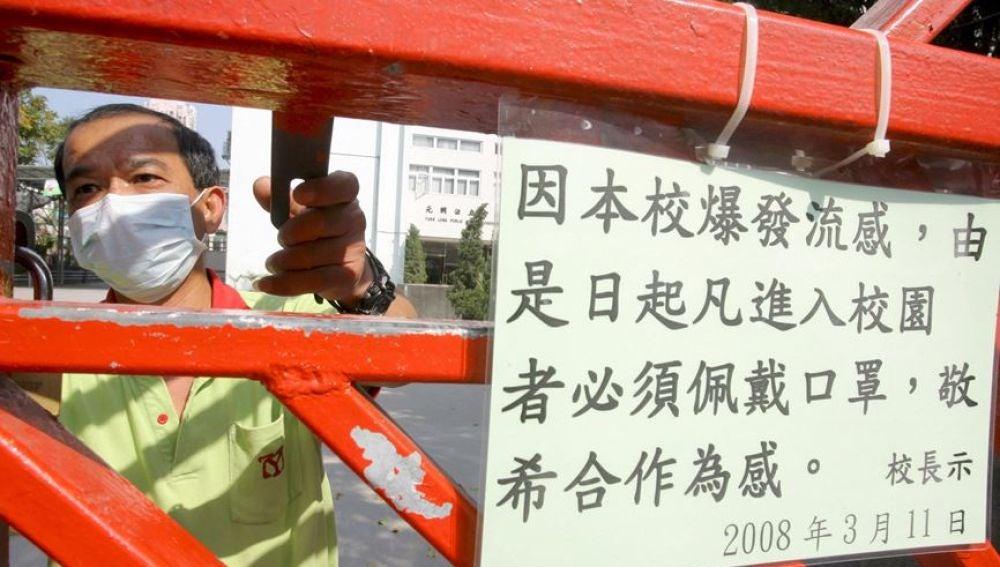 Un trabajador de un colegio con una máscara cerraba las puertas del centro educativo con un cartel del Ministerio de Sanidad, por un brote de gripe.