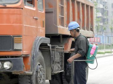 Imagen de un trabajador desinfectando los bajos de un camino en Pekín, China.