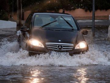 Un vehículo sumergido en el agua durante el temporal