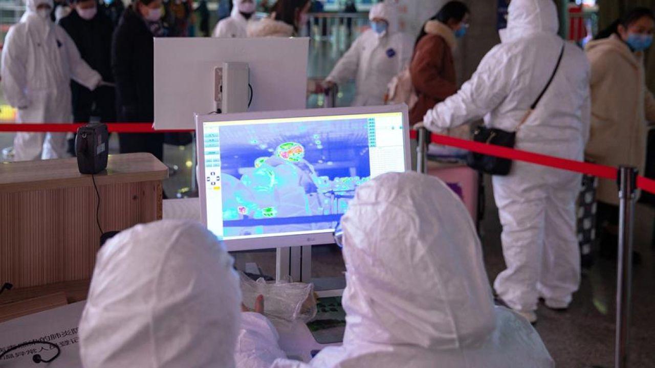 Personal revisan la temperatura de los pasajeros en un aeropuerto