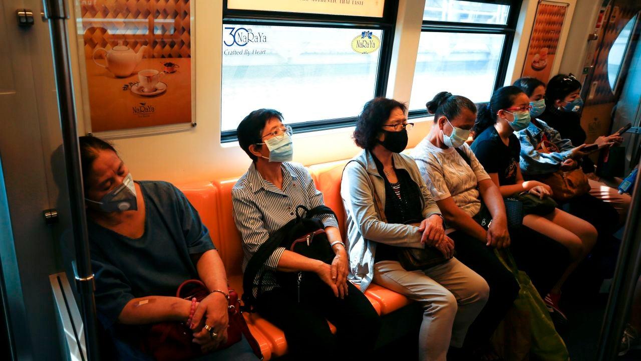 Pasajeros viajando en un tren de Bangkok, en Tailandia