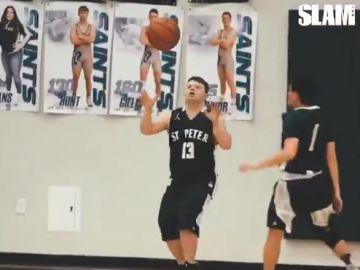 Un niño con síndrome de down jugando al baloncesto.