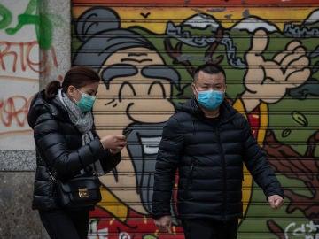 Dos personas con mascarillas por miedo al coronavirus.