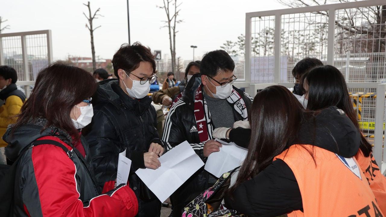 Aficionados entrando a un partido de fútbol protegiéndose del coronavirus