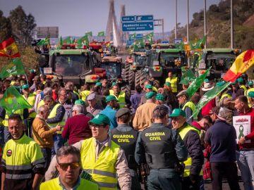 Agricultores junto a parte del más de un centenar de tractores y otros vehículos agrícolas durante el corte de tráfico en la autovía A-49corta la frontera con Portugal en Huelva