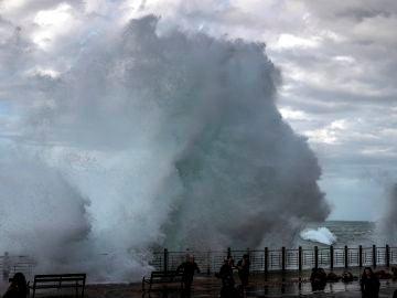 Varias personas son sorprendidas por una gran ola rompiendo en el Paseo Nuevo de San Sebastián