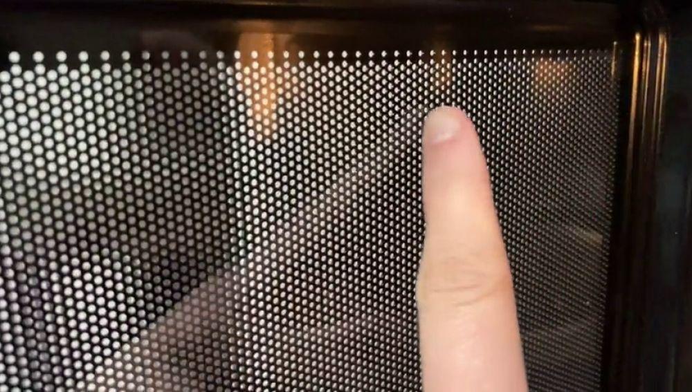 Para qué sirve la malla con agujeros de la puerta de los microondas