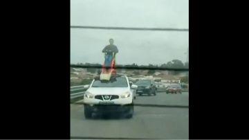 Un hombre subido a un tobogán en el techo de un coche en Chiclana