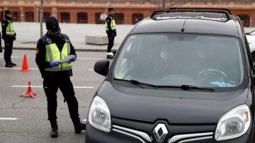 Un policía revisa la documentación de un vehículo en un control de seguridad