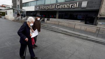 Dos personas mayores con mascarillas frente al Hospital de La Paz