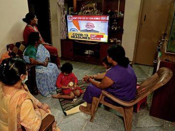 Una familia india escucha en la televisión el discurso del primer ministro sobre la alerta por COVID-19.