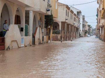 Un vecino de Los Alcázares observa desde su casa su calle inundada a causa de las fuertes lluvias caídas sobre el Campo de Cartagena
