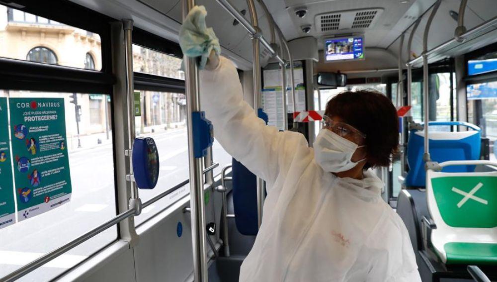 Una operaria de limpieza desinfecta un autobús urbano de San Sebastián.