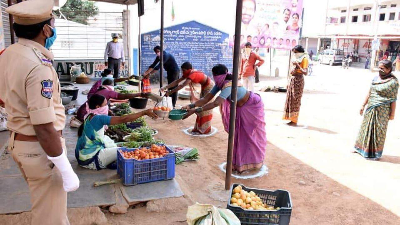Ciudadanos sale a hacer la compra bajo medidas de seguridad durante el confinamiento en la ciudad india de Anantapur.