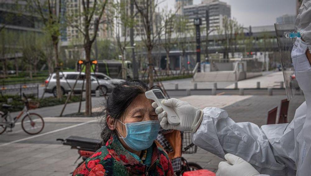Un sanitario verifica la temperatura de una anciana a la entrada de un banco en Wuhan