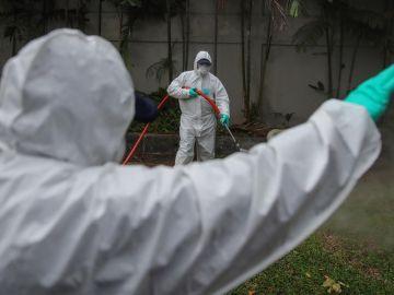 Los funcionarios de salud con trajes protectores rocían desinfectante.