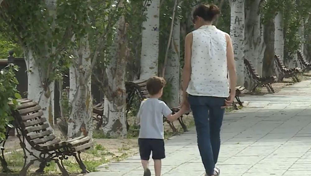 Una mujer pasea con un niño por la calle