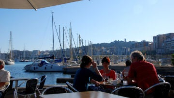 Gente disfrutando de una terraza frente al mar, en el Paseo Marítimo de Palma.