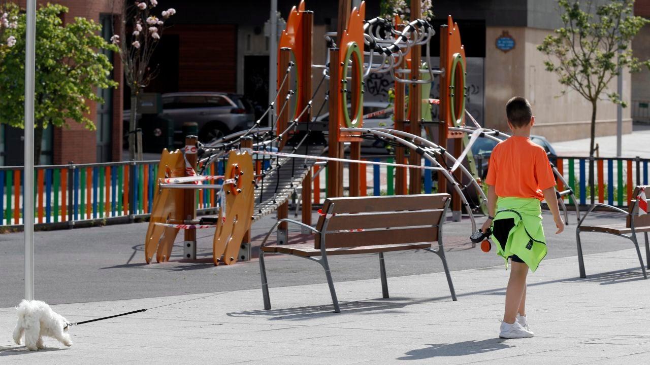Un niño pasea el perro junto a un parque cerca de su casa en Bilbao
