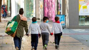 Fotografía de archivo de una madre y sus hijos tras hacer la compra en Zaragoza