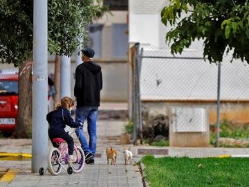 Una niña pasea junto a su padre en bicicleta