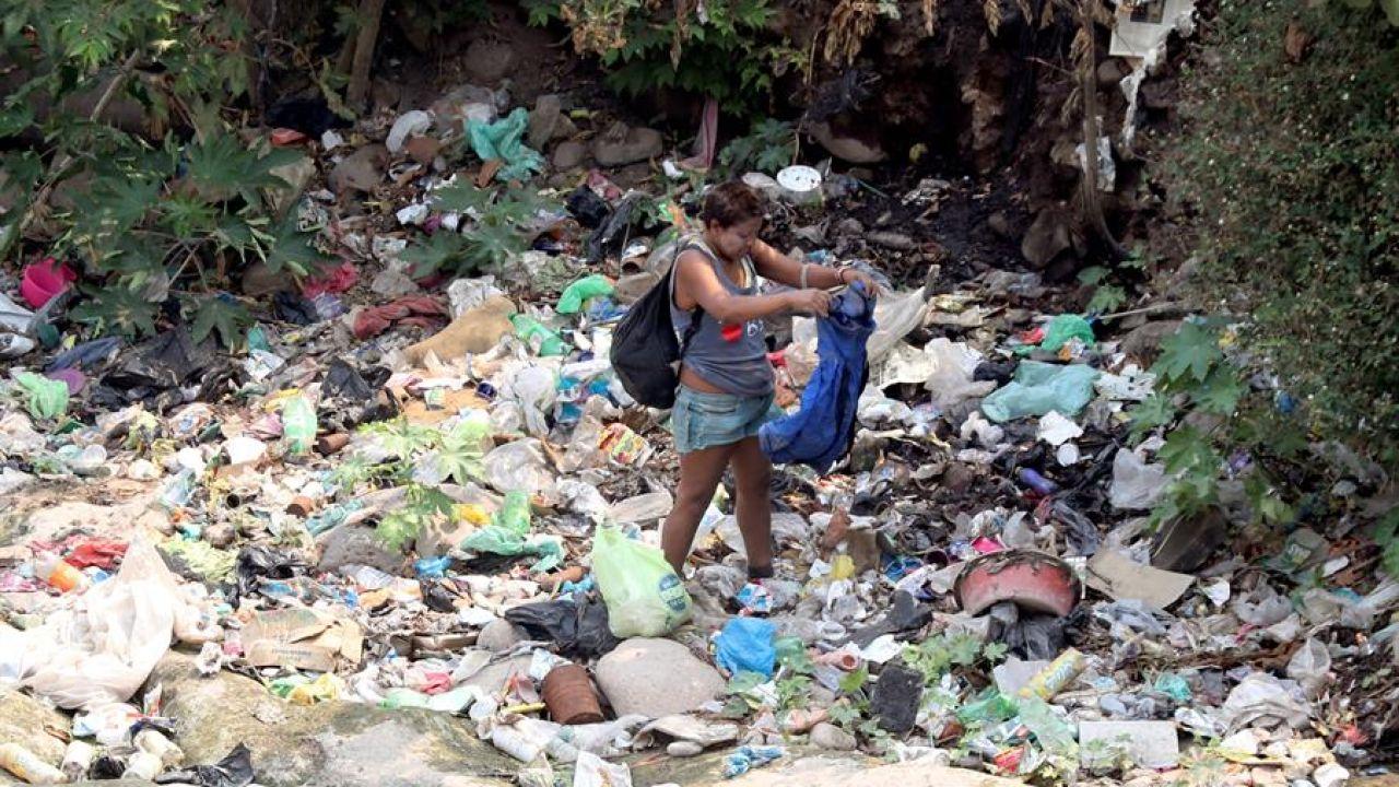 Una mujer busca entre la basura en Tegucigalpa (Honduras)