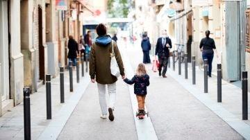 Un hombre y una niña caminan por el barrio de Gracia