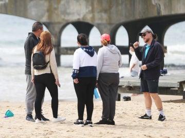 Un guardacostas habla con una familia en Bournemouth que acude a la playa en pleno confinamiento