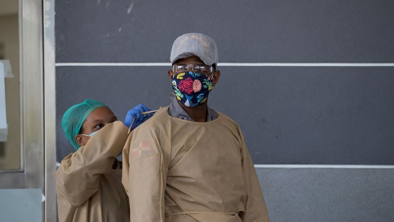 Una enfermera ayuda a un policía a cubrirse, mientras controlan el acceso al hospital Moscoso Puello este viernes, en Santo Domingo (República Dominicana), donde estas últimas semanas varias personas fueron ingresadas tras consumir consumo de clerén