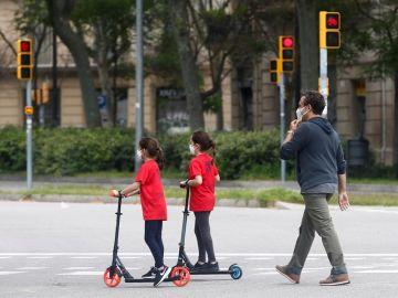Un hombre y sus dos hijas caminan por una calle de Barcelona