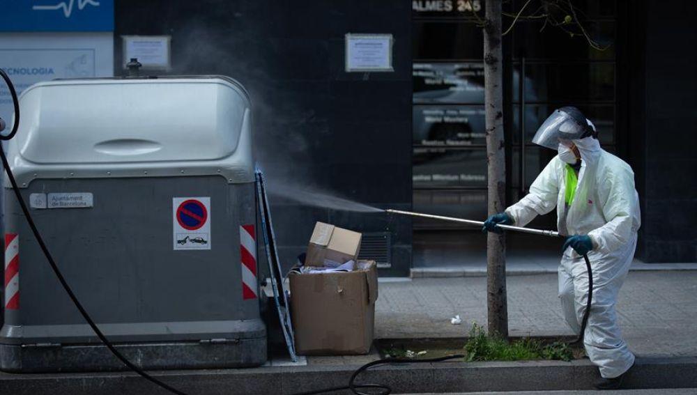 Un operario desinfecta un contenedor de basura en Barcelona