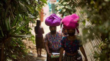 Mujeres con mascarilla portan alimentos entregados como ayuda alimentaria en Guatemala